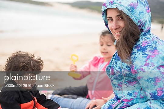 Mother and children playing at a windy beach - p300m2012616 von Jaen Stock