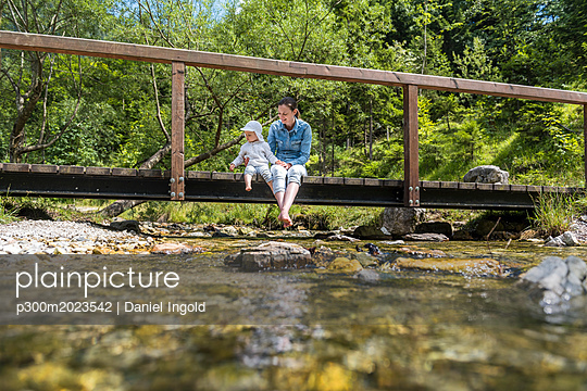 Mother and daughter sitting on wooden bridge, mountain stream - p300m2023542 von Daniel Ingold