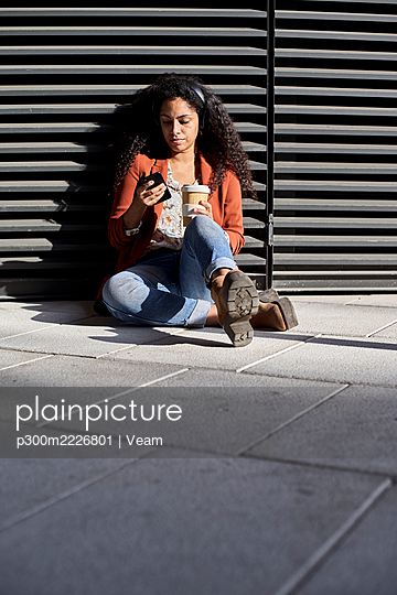 Woman using smart phone holding coffee cup while sitting against shutter - p300m2226801 by Veam