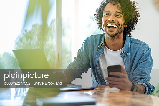 Cheerful businessman holding smart phone while sitting with laptop at home - p300m2277592 by Steve Brookland