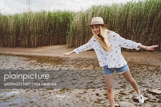 Attraktive junge Frau balanciert auf Steinen - p432m2217467 von mia takahara