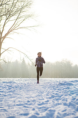 Young woman jogging in winter landscape - p1026m1025119f by Patrick Frost