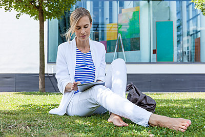 Blond businesswoman using tablet sitting on meadow - p300m2023690 by Tom Chance