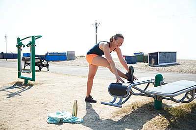 Smiling sportswoman doing stretching exercise in outdoor gym on sunny day - p300m2226437 by Pete Muller