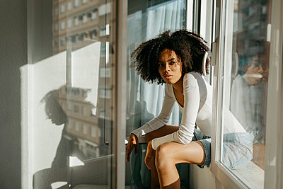 Confident woman with curly hair sitting on window sill at home - p300m2268145 by Tania Cervián