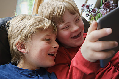 Close-up of happy brothers using digital tablet at home - p301m1180577 by Halfdark