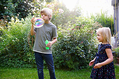 Boy and girl blowing bubbles - p4294958f by Ghislain & Marie David de Lossy