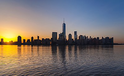 Silhouetted view of Manhattan financial district skyline at sunset, New York, USA - p429m1095121f by Henglein and Steets