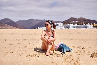 Woman using headphones on beach - p890m2099705 by Mielek
