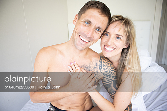Couple in love sitting on bed, portrait - p1640m2259580 by Holly & John