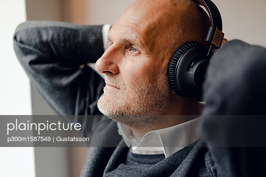 Senior man wearing headphones, listening music, portrait - p300m1587549 von Gustafsson