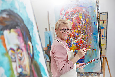 Portrait smiling female artist painting at canvas in art class studio - p1023m1506497 by Agnieszka Olek