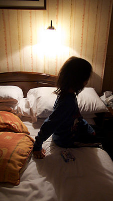 Child sitting on bed in atmospherically lit room - p1072m829532 by Tracy Jean Shields