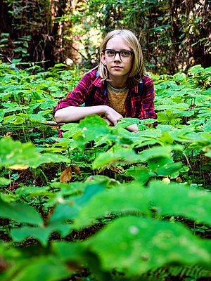 Young boy crouching in clover field in redwood forest - p1166m2137364 by Cavan Images