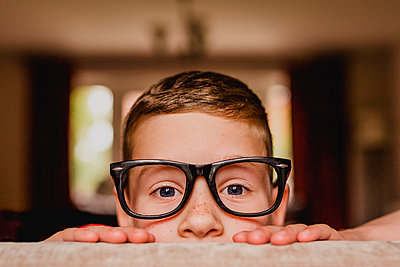 Portrait of peeking boy wearing oversized glasses - p300m1449237 by Nicole Matthews