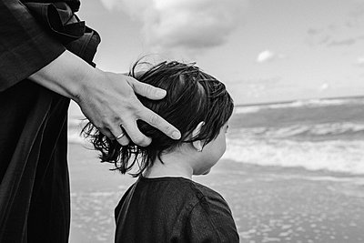 Mother's hand touching little daughter's hair on the beach - p300m2170681 by Oxana Guryanova