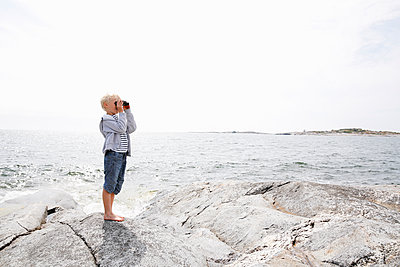 Sweden, Stockholm Archipelago, Sodermanland, Orno, Boy (6-7) standing on rocky seashore and looking through binoculars - p352m1349495 by Jenny Lagerqvist