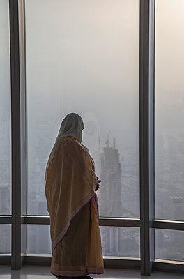 Asian woman at window admiring Dubai cityscape, Dubai Emirate, United Arab Emirates - p555m1410834 by ac productions