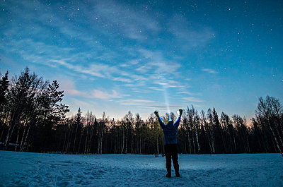 Caucasian man wearing headlamp with arms raised in winter - p555m1491036 by Aleksander Rubtsov