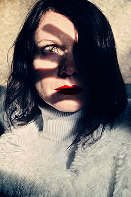Portrait of woman with shadow across face  - p577m2055188 by Mihaela Ninic