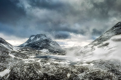 Storm clouds over Olaskarsvatnet lake at feet of the snowcapped Olaskarstind mountain, Venjesdalen valley, Andalsnes, Norway, Scandinavia - p871m2143253 by Roberto Moiola