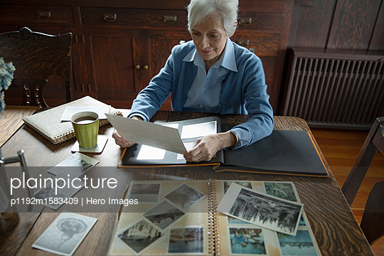 Senior woman with coffee looking through photo album at home - p1192m1583409 by Hero Images