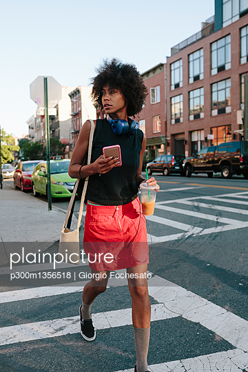 Young woman with headphones and smart phone crossong street in Brooklyn, carying take away drink - p300m1356518 by Giorgio Fochesato