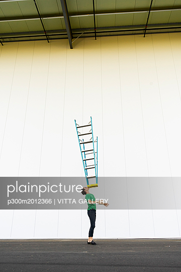 Acrobat balancing ladder on his face - p300m2012366 von VITTA GALLERY