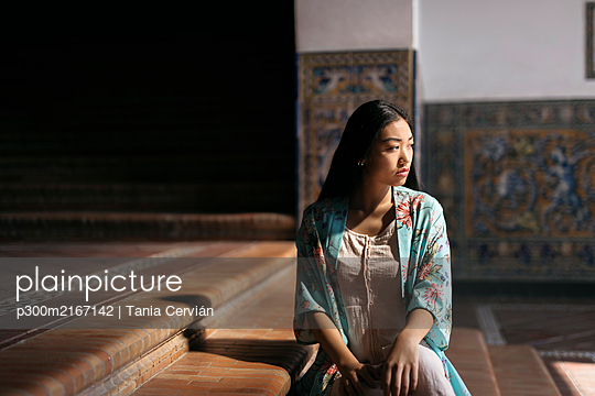 Portait of beautiful young woman sitting on steps wearing a kimono - p300m2167142 by Tania Cervián
