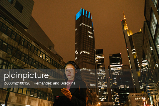 Young woman using tablet in the city at night, Frankfurt, Germany - p300m2188126 by Hernandez and Sorokina