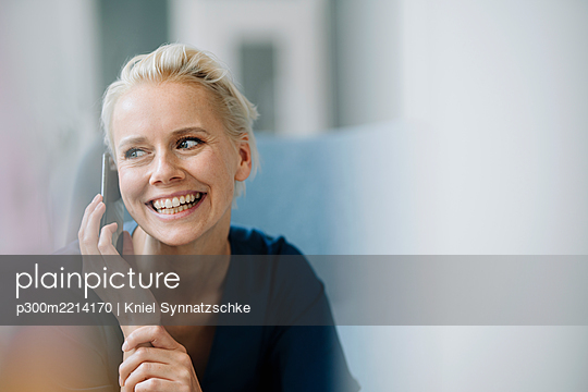 Close-up of cheerful businesswoman talking over smart phone while sitting in office - p300m2214170 by Kniel Synnatzschke