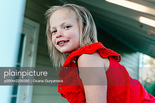 Smiling girl standing against residential building - p300m2226392 by Oxana Guryanova