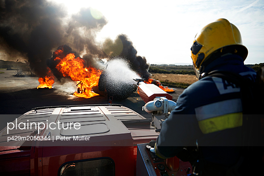 Fireman putting out fire on old training aeroplane, Darlington, UK - p429m2058344 by Peter Muller