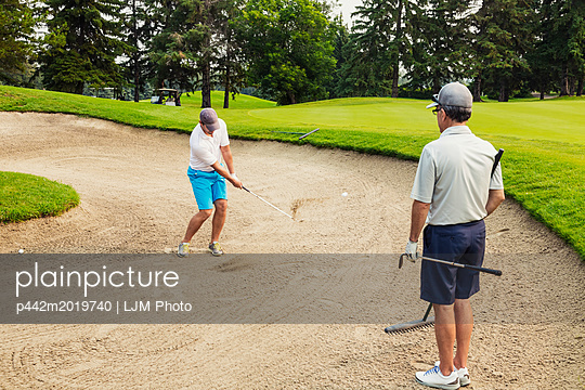 Two male golfers standing in a bunker, one holding a rake and waiting his turn, while the other swings at the ball to chip it out of the sand pit; Edmonton, Alberta, Canada - p442m2019740 by LJM Photo