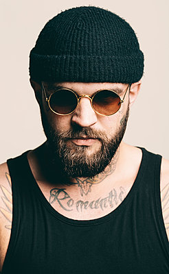 Portrait of confident man wearing sunglasses against gray background - p1166m1546925 by Cavan Images