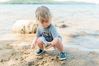 Little girl playing with sand on a rocky New England beach. - p1166m2153713 by Cavan Images