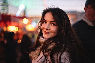Portrait of happy teenage girl walking in Christmas market in city - p1166m2189652 by Cavan Images