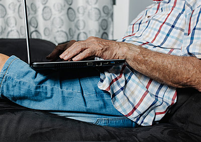 Aged man using laptop on sofa - p1166m2218567 by Cavan Images