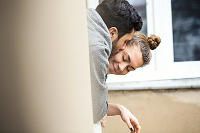 Seitenansicht eines jungen Paares, dass sich kuschelnd aus einem Fenster lehnt  - p1301m1424727 von Delia Baum