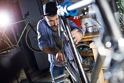 Man working on bicycle in workshop - p300m1563380 by Josep Suria