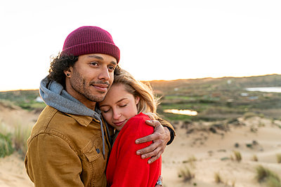 Woman with eyes closed embracing man while standing against sky - p300m2268021 by Steve Brookland