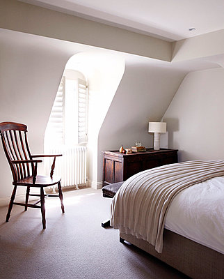 Wooden chair at dormer window in cream bedroom - p349m790263 by Brent Darby