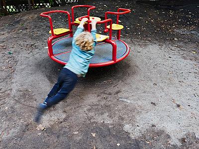 Junge schwingt am Karussell - p358m1516361 von Frank Muckenheim