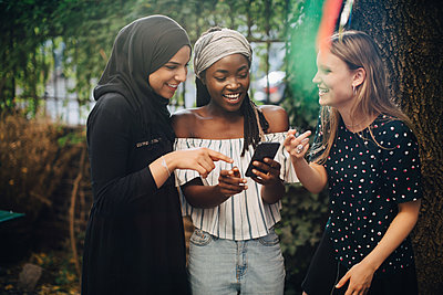 Smiling multi-ethnic female friends looking at mobile phone while standing in backyard - p426m2046241 by Maskot