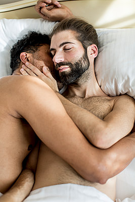 Gay couple in bed  - p787m2115262 by Forster-Martin