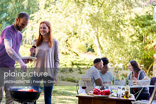 Young man preparing food in barbecue grill while his friends have a drink in background - p623m2294755 by Frederic Cirou