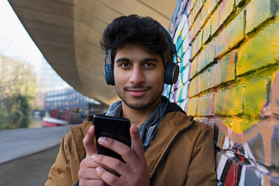 Portrait confident young man listening to music with headphones and mp3 player - p1023m2161736 by Tom Merton