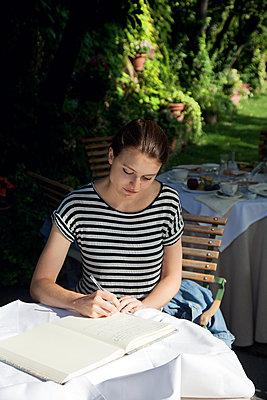Frau schreibt im Garten - p1356m1475026 von Markus Rauchenwald
