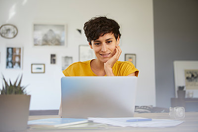 Portrait of smiling woman at home sitting at table using laptop - p300m2062562 by Rainer Berg