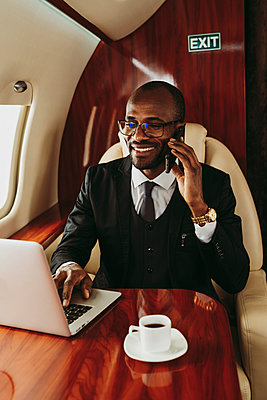 Smiling businessman talking on smart phone while using laptop in private jet - p300m2257066 by OneInchPunch